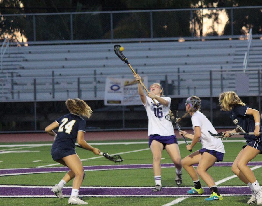 Junior, Maggie Sweeney reaches for the ball, gaining control after the draw. On Tues. Apr. 9 Carlsbads varsity womens lacrosse team played against the LCC Mavericks. The final score was 2-12 LCC.