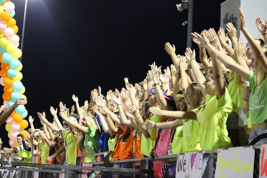 Members of Loud Crowd clap there hands together for there lancers. On Friday, September 23 loud crowd members dress in all neon as Carlsbad plays La Costa in a hard fought battle.