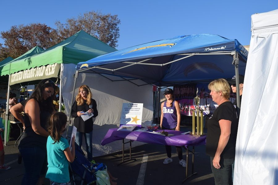 Sophomore, Ella Pines hands out flyers promoting the Junior Lancer Dancers's Camp and their annual golf tournament. At the farmer's market last Wed. Oct. 12, the Lancer Dancer's held an info booth for their team.