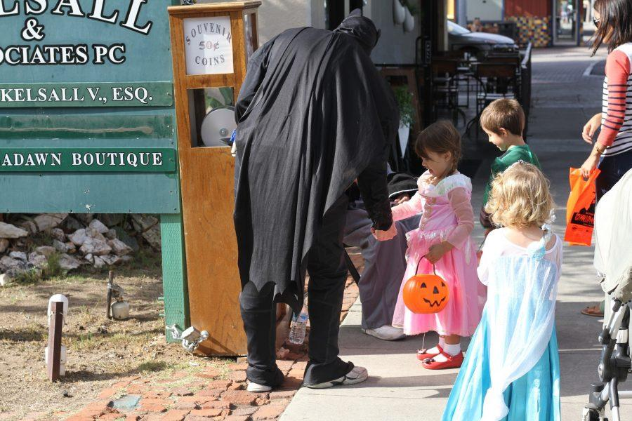 Children dressed up stop by a station to receive souvenir coins. For just $0.50, a coin could be made to remember the C3 Halloween in the Village.