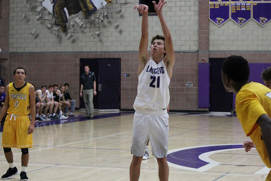 Senior Stone Stapleton shoots free throws at the first home basketball game of the year on November 30th. The Loud Crowd showed its support throughout the night with a USA theme.