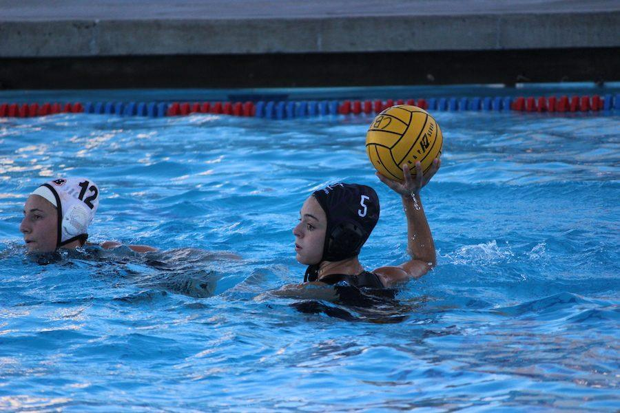Junior, Amy Coval passes the ball assisting a Carlsbad goal. Tues. Feb. 7 the Lancers girls water polo played the Huntington Beach Oilers in their second to last game before CIF playoffs. Carlsbad High came out with a win 13-5.