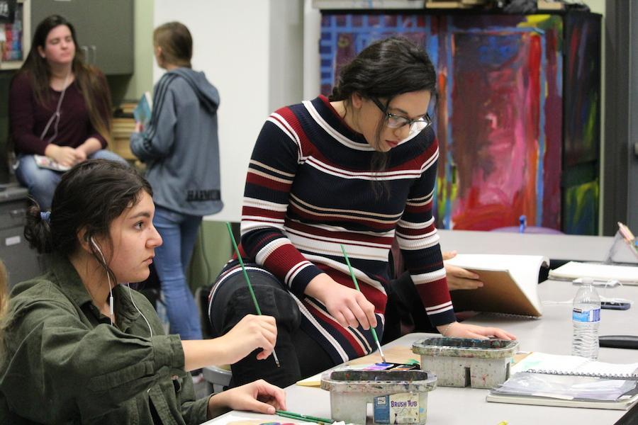 Seniors Danika Lara, Samantha Tucker work on their current art work during their third period AP art class.