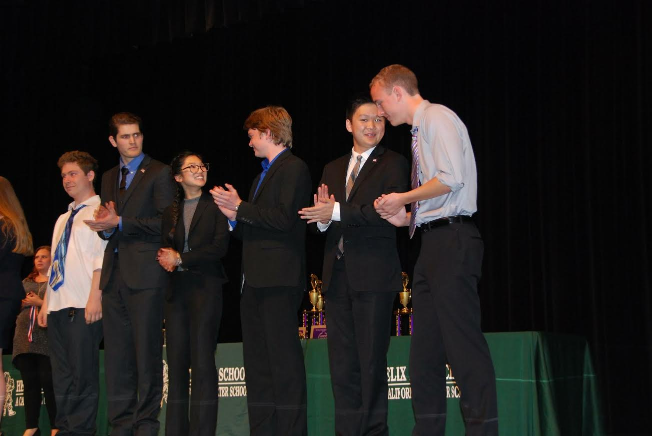 Members of Carlsbad High School's nationally ranked speech and debate team stand on stage waiting to accept awards for the events that they placed in.