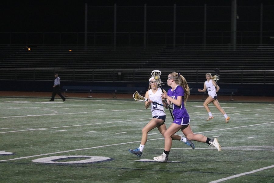 Mackenzie Frost uses her speed to drive to goal against opponent, San Marcos High. Thursday, March 2, girls lacrosse played their first game of the season, in which they won by a score of 9-6.