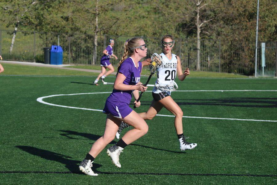 Senior, Mackenzie Frost takes on a Pacific Ridge defender during her drive down the field. Thursday, March 9, Carlsbad girls lacrosse played Pacific Ridge, where they pulled out the win.