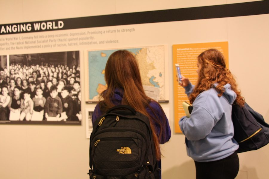 Two students take pictures of the exhibit in the Holocaust Center for Humanity.