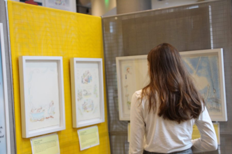 Student stops and admires the drawings in the Curious George exhibit. The art pieces symbolize happiness and serenity.