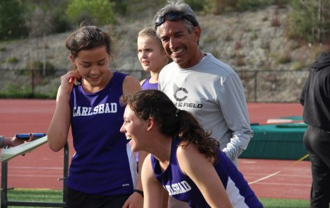 Coach Manny congratulates senior Sam Schneider as she finishes the 4X400 relay race at Sage Creek
