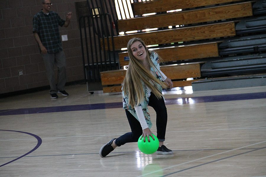 Senior Julia Taliana picks up a lose ball and prepares to return the shot.  Talianas team decided to wear Hawaiian shirts which brought some island flare to the court.