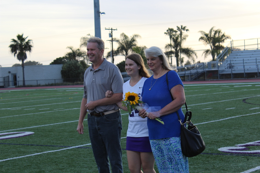 Senior and varsity lacrosse player, Megan Cowles walks with her parents down the center of the field. Thurs. Apr. 27 Carlsbad High's womens lacrosse team celebrated their senior night with a game against San Dieguito Academy.