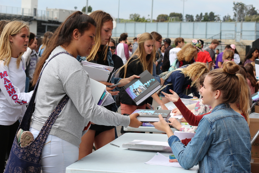 Students of all grades rush behind the new gym to receive their 2016-2017 yearbooks  on Thursday. Yearbook staff worked really hard to give the students a memorable book to reflect their high school career.