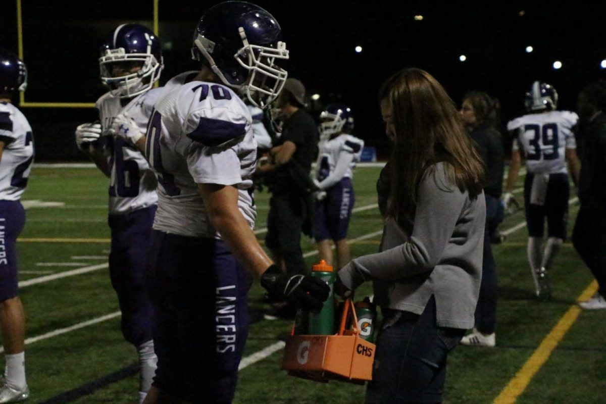 Junior, Trinny Liu, gives water to senior, Logan Plasch, at varsity football's away game at LCC on Friday, Sept. 22. As an athletic trainer, one of Liu's responsibilities is to ensure players are well hydrated during their games.