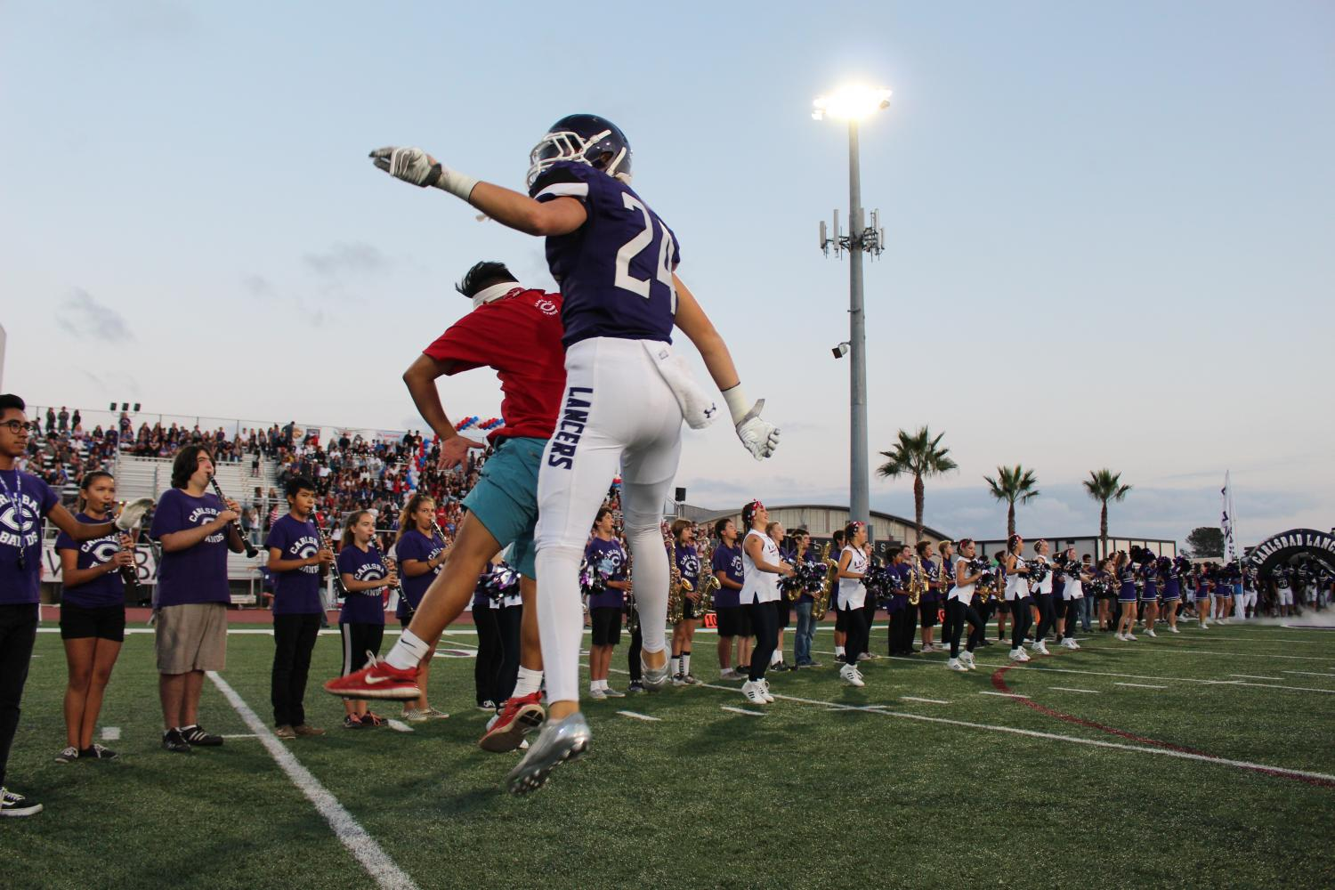 Sophomore, Colbie Whillock, jumps his way onto the field for his game against Mission Hills.