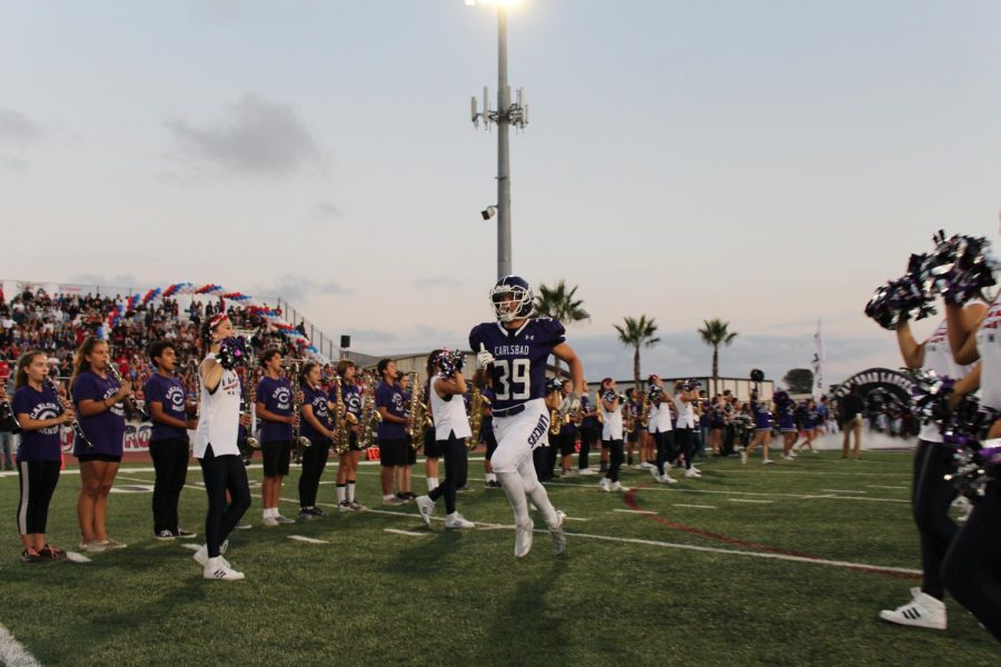 Sophomore, Noah Vella, runs onto the field ready to play Mission Hills during the USA football game.