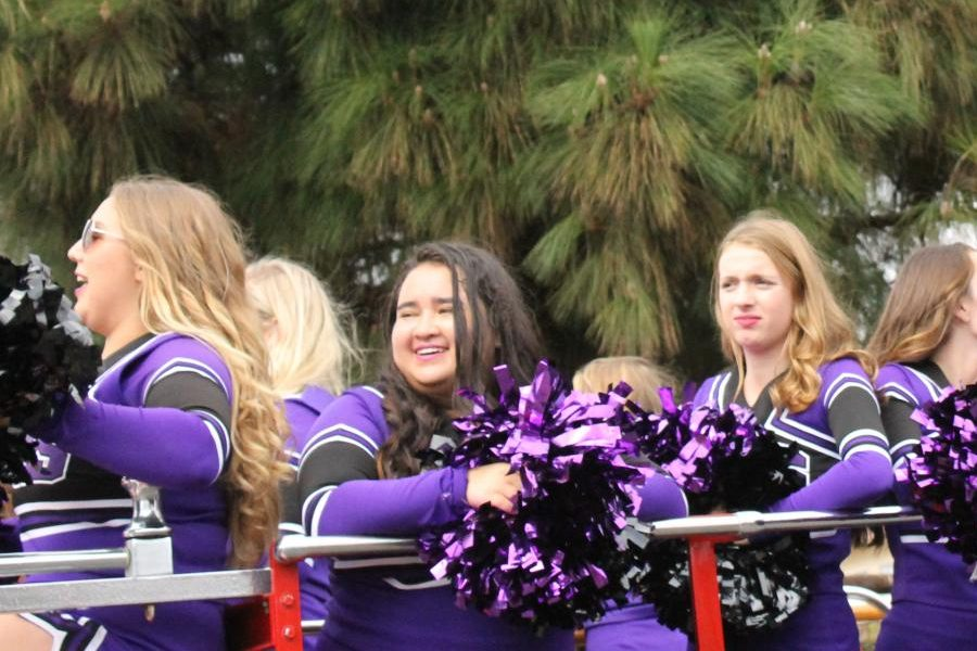 Varsity cheer rides on a float in the Lancer Day Parade. The varsity cheer team was showcased along with many other school groups and sports.