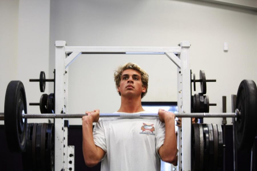 Senior, Izaac Desoto, concentrates on getting in reps during weight  training class, Tuesday, Oct. 3, 2017. Desoto is a part of the before school weight training class for aquatics and water polo.