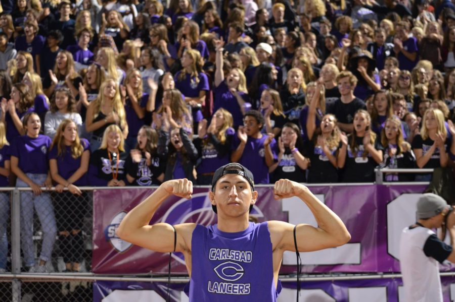Senior Chris Weedman flexes for the camera, as he stands in front of hundreds of students in Loud Crowd. Students were all wearing purple for the homecoming game.