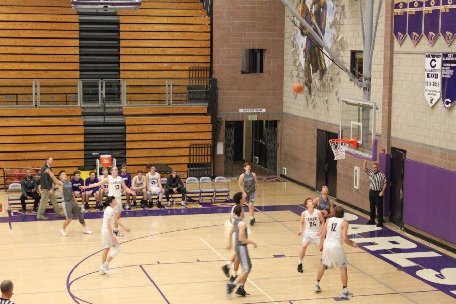 The varsity basketball team prepares to grab a rebound.