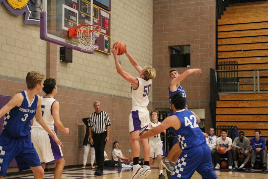 Sophomore Jackson Payne grabs the rebound, Saturday, Dec. 2. JV basketball beat La Jolla Country Day 52-47.
