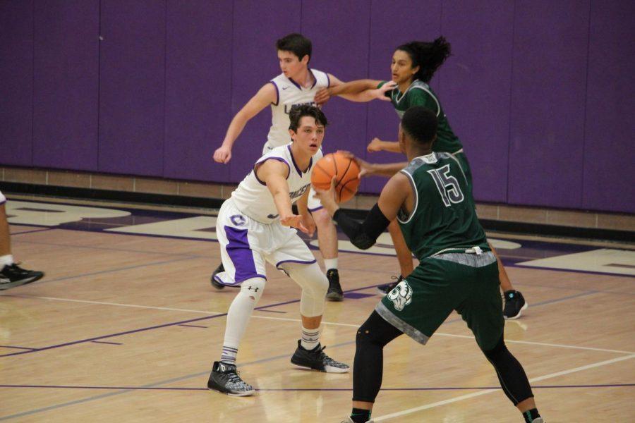 Sophomore Kyle Vassau guards a member of the Murietta Mesa JV team, Tuesday, Nov. 28. The JV basketball team beat Murrietta Mesa 56-51 after going into double overtime.