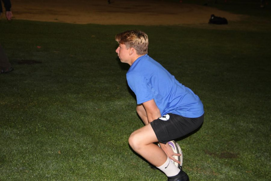 Sophomore Grant Brownell, varsity rugby player, holds position to initiate the scrimmage. Grant makes an inceptive connecting pass to one of his team members.