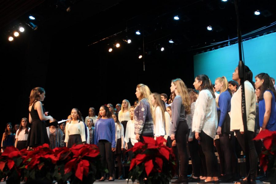 Choir students gather to sing a song together at their winter show. The winter show included individual performances and sets from each of the three choirs.