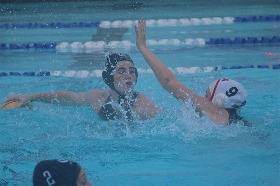 Junior Meave Murphy looks to pass the ball as she is blocked by a member of the opposing team. Murphy is a member of the varsity women's water polo team.