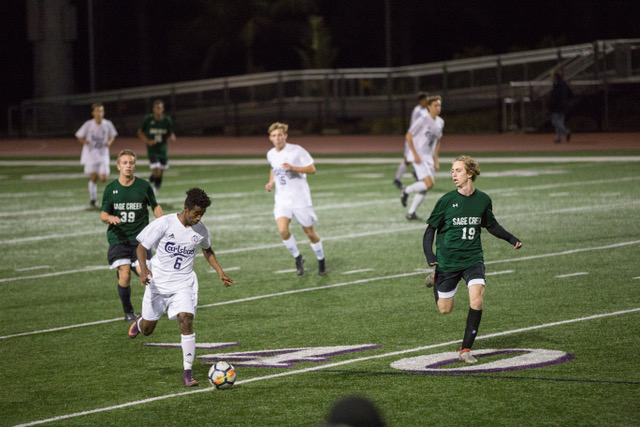Senior Aman Mikel dribbles up the field looking to dribble past some Sage Creek players during the Varsity game Friday Feb. 16. The Lancers went on to beat the Bobcats  1-0.