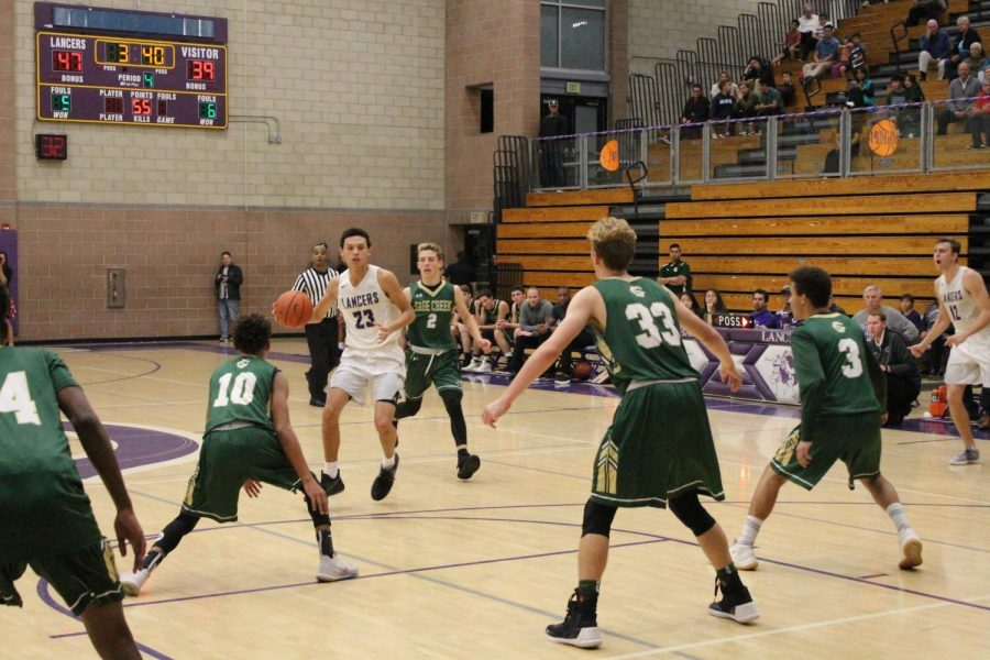 Junior Carter Plousha drives down the court looking for opportunity from his teammates in the paint. This is Carters second year playing on varsity basketball for Carlsbad