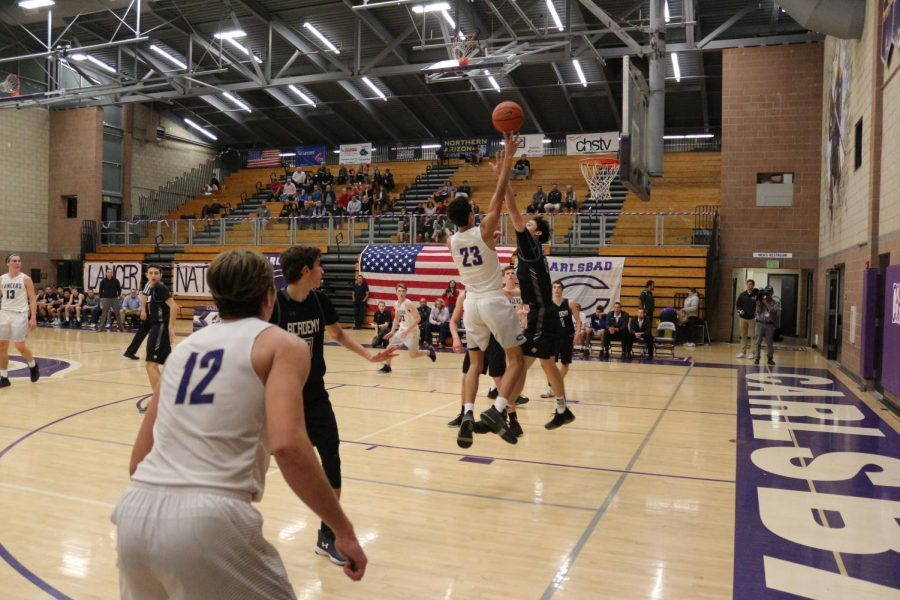 Junior Carter Plousha jumps up for the layup to tie the game. CCA defense tries block him at the peak of his jump.