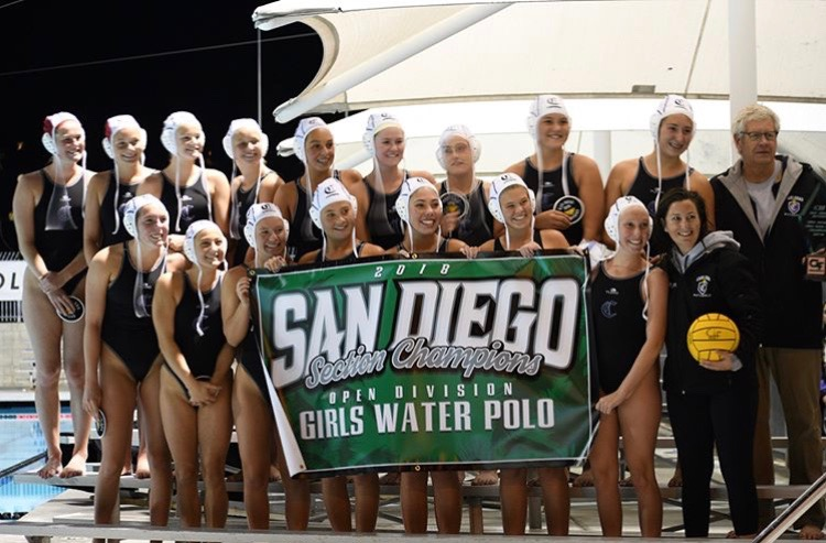 Girls water polo holds up their championship banner in victory. The girls are CIF champs of open division.