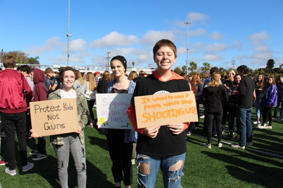 Sophomore Dylan Phillips is all smiles holding his homemade sign with his friends support for the walkout. The sign brings some humor to the unfortunate topic.
