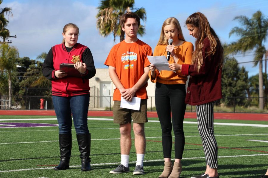 Junior Kate Ellis speaks in front of all the walkout participants honoring those affected to gun violence. Senior Dillan Krichbaum, Junior Mackenzie Ogden, and Junior Gracie Landry stand by her side as she performs her speech.