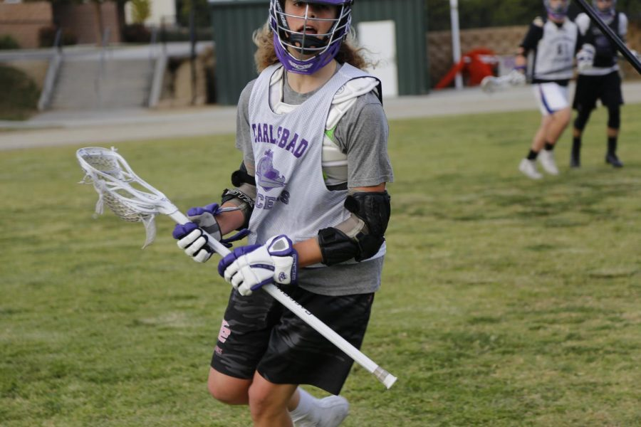 Sophomore Tommy Lombardi practices with the varsity lacrosse team for upcoming games.
