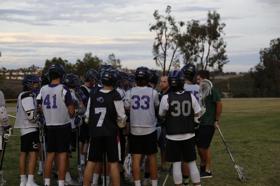 The lacrosse team huddles up for a pep talk from coach Dave Demuth. They hope to win the upcoming games in the near future.