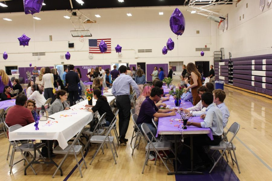 Team and family members sit down at the tables to begin the ceremony.