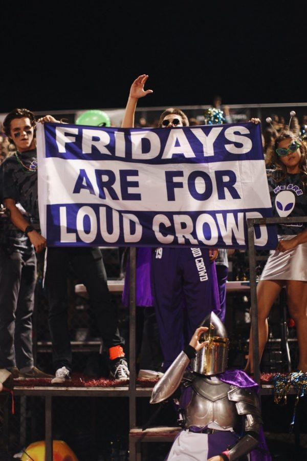Loud Crowd holds up the Fridays are for Loud Crowd sign. The rest of the students in the crowd cheer in the background.