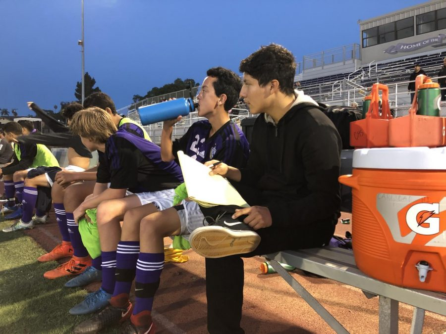 Jeo Canseco-Galan watches the JV boy's soccer game and writes down the stats of each player.