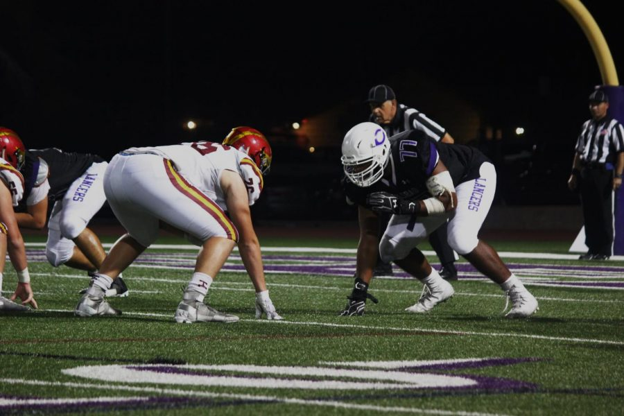 Senior Carlos Harrison readies for the snap against his Torrey Pines opponent. He has committed to University of Wyoming and received a large scholarship.