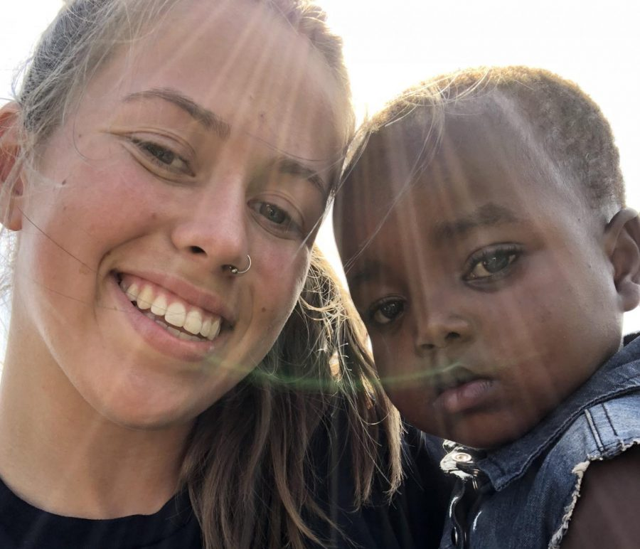 Kelly Frost, senior, shares a moment with the kids that Kids For Peace helped in Kenya.