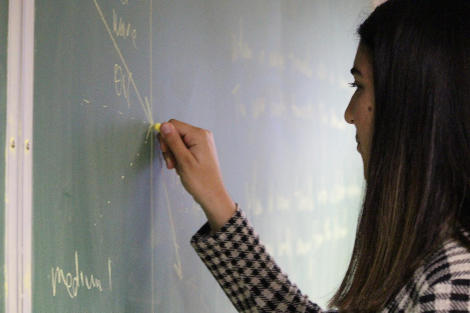 Shayda Moezzi, 11, figures out a physics problem in her AP physics class.