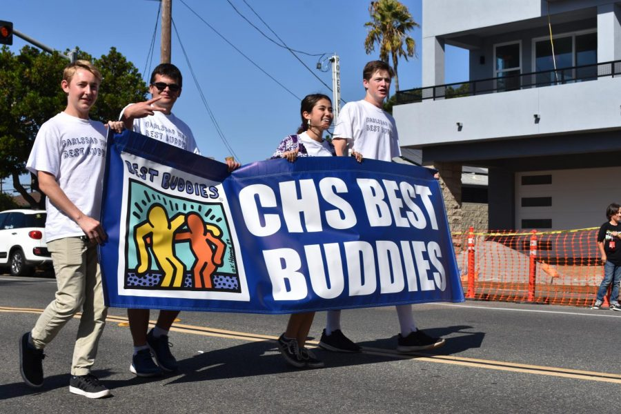 Members of the Best Buddies club walk in the parade holding their club banner. Best Buddies was one of multiple clubs who participated in the parade.