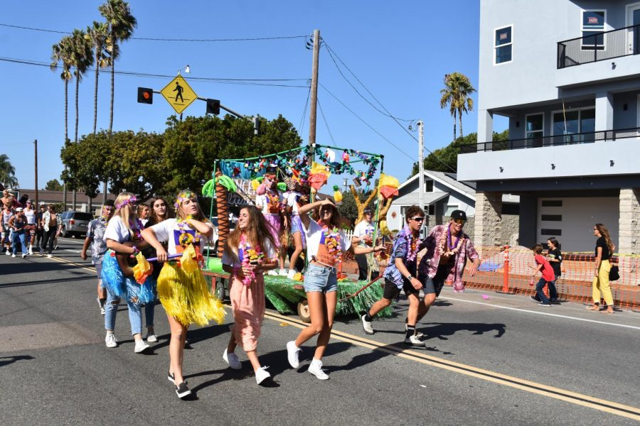 Members of the junior class dance around their Luau themed float. The junior float ended up winning first place in the contest.
