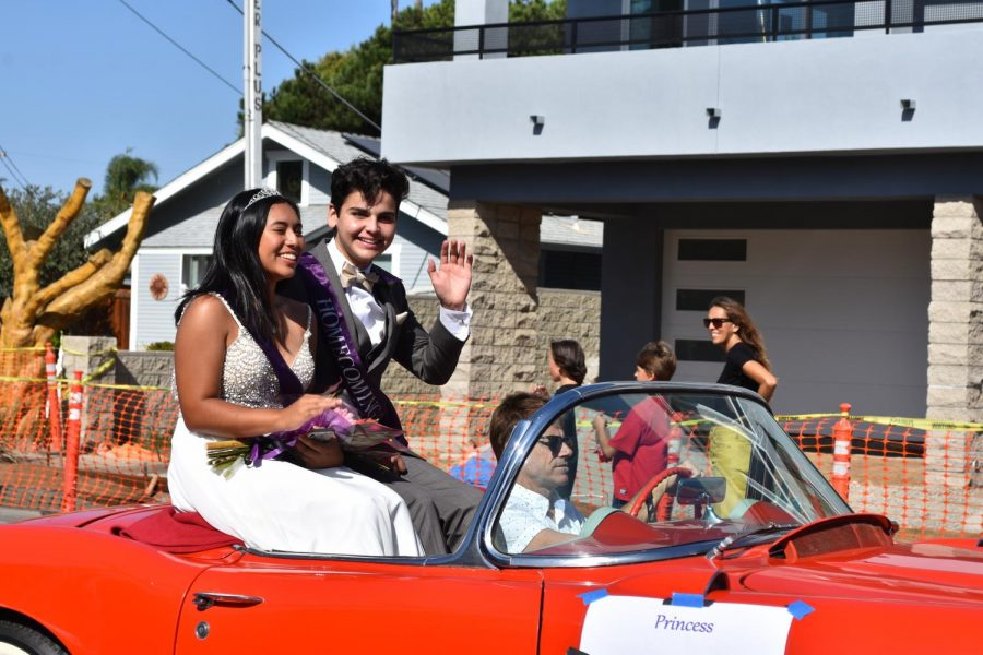Seniors Shayla Eslampour and Ethan Long are waving to the crowd at the Lancer Day Parade. Eslampour and Long were one of the five pairs nominated to become the homecoming queen and king.
