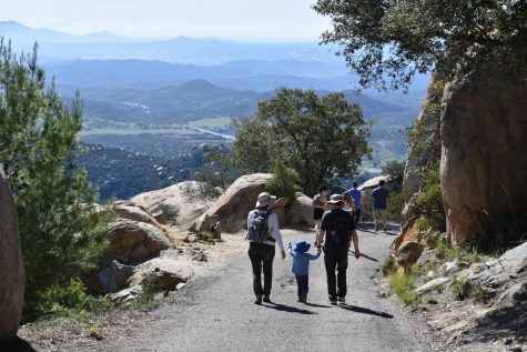 A family hikes down the mountain after seeing the famous rock. Although the hike is difficult people of all ages can complete the hike.