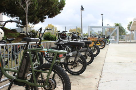 During school hours, a row of e-bikes line the bike racks inside of the Carlsbad High School campus.